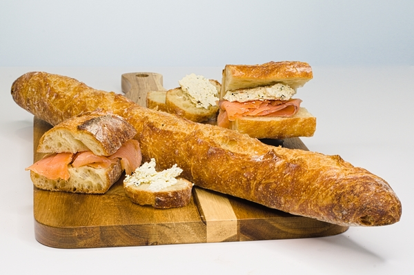 Charcuterie featuring salmon and spiced cheese with a baguette
