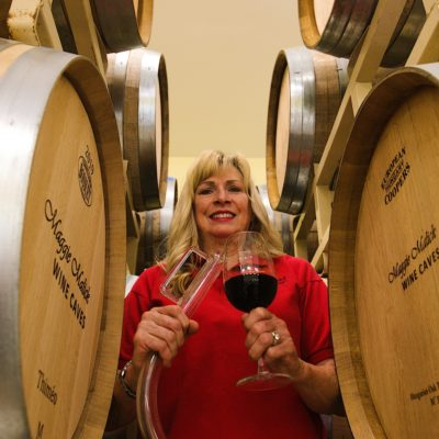 Maggie Malick in the racks of barrels holding a wine thief