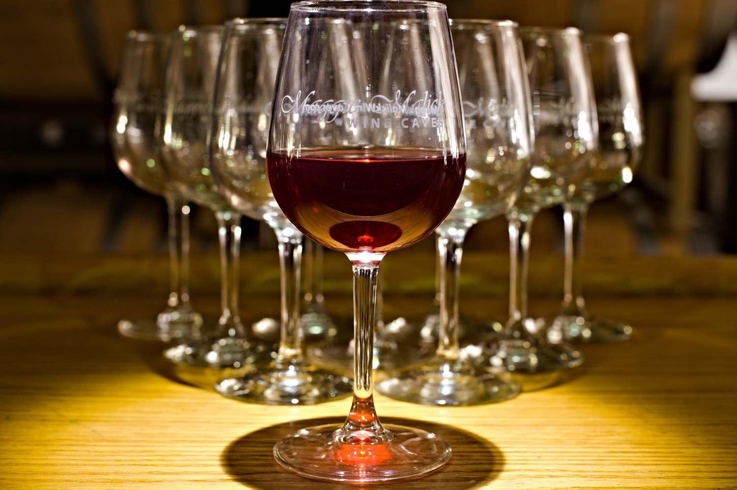Artistic arrangement of glasses at the bar at Maggie Malik wine caves featuring red wine