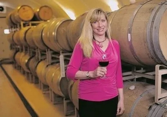 Maggie Malick in the wine cave holding a glass of wine