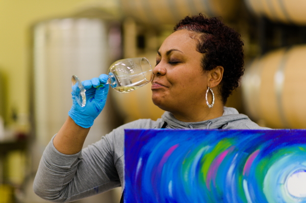 Tee showing painting and enjoying Chardonnay