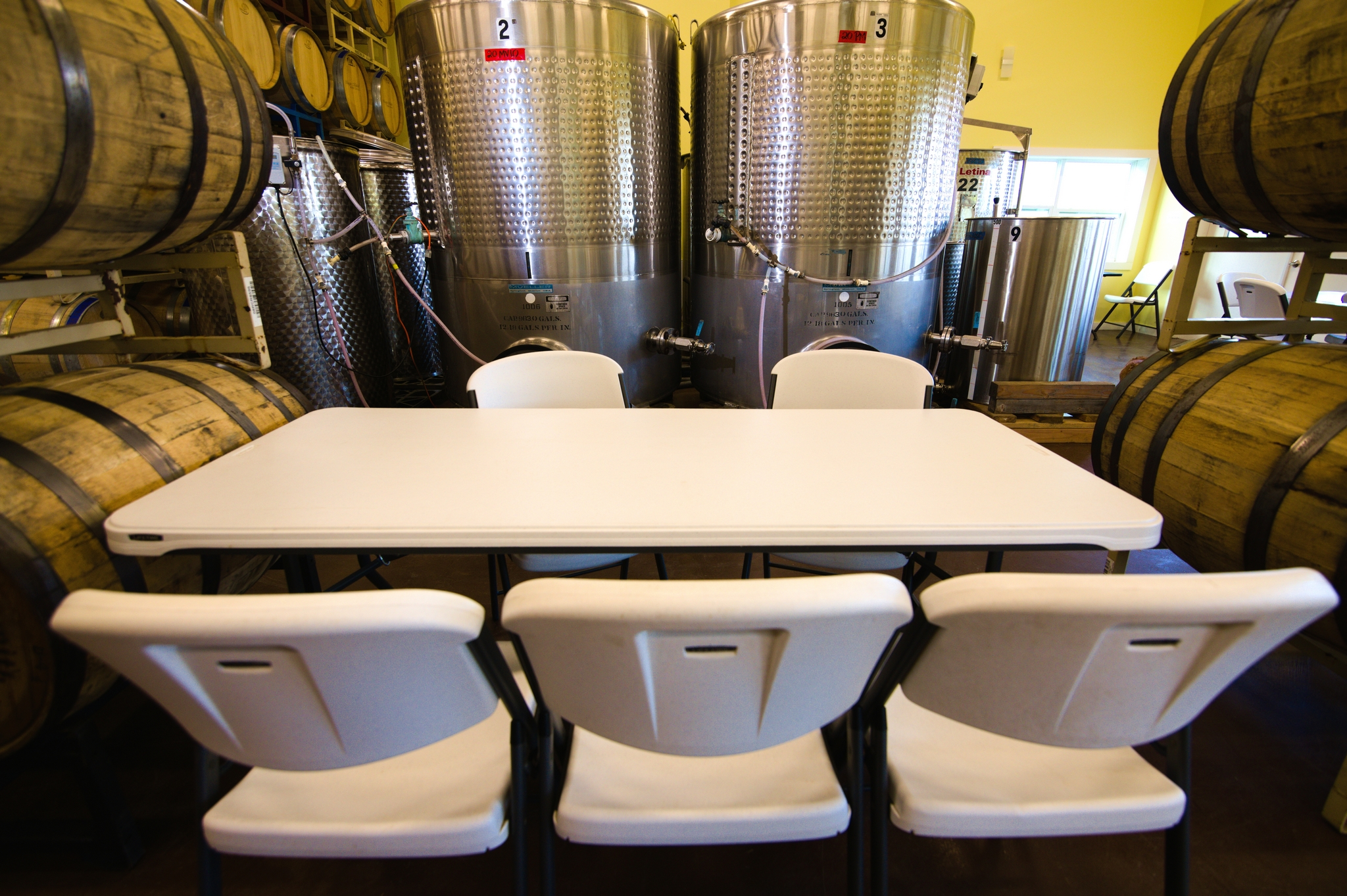 Table and chairs surrounding by barrels and tanks